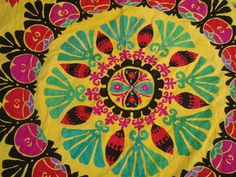 This authentic Uzbek Suzani has stunning hand-embroidered circular floral designs in vibrant turquoise, red, pink and black on a yellow fabric.