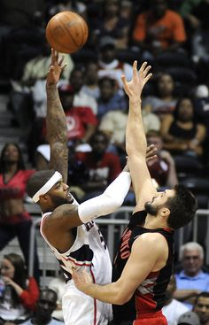 Atlanta Hawks forward Josh Smith (L), attempts to shoot over the defense of Toronto Raptors forward Linas Kleiza (R), in the first half of their NBA basketball game in Atlanta, Georgia April 15, 2012.