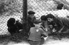 """Family members say goodbye to a child through a fence at the Lodz ghetto's central prison where children, the sick, and the elderly were held before deportation to Chelmno during the """"Gehsperre"""" action. Lodz, Poland, September 1942."""