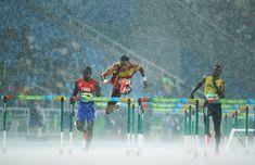 Jhoanis Portilla of Cuba, Orlando Ortega of Spain and Deuce Carter of Jamaica compete in the rain during the 2016 Rio Olympics Men's 110m Hurdles in Rio de Janeiro, Brazil, Aug. 15, 2016.