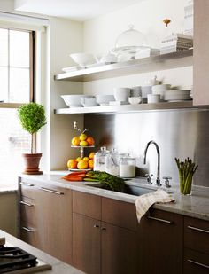Neutral kitchen with oranges, greenery, and open shelving // the home of fashion designer Peter Som