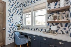Blue contemporary home office boasts a built in navy blue desk fitted with polished nickel cup pulls and a light gray quartz countertop seating a blue linen desk chair facing a window dressed in a natural linen roman shade accenting walls covered in Thibaut Birding Wallpaper as stacked salvaged wood floating shelves are mounted beside the window.