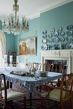 Traditional country dining room in Dining Room Design Ideas. Dining room decorated with blue scheme, wall mounted plates, chandelier and wooden furniture in neoclassical pavilion.