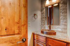 Powder room with stone surrounding bathroom mirror Custom vessel sink
