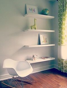 White wall shelves with plenty of space between them draw the eye up and make the room feel bigger.