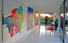 Love these giant paintings and the floor is red brick coated in epoxy.
