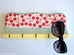 Turn a fishing rod rack into a DIY sunglass holder. Dressed up in pastel hues and girlie prints, notches meant to hold fishing gear are also perfect for hanging sunglasses next to your vanity.