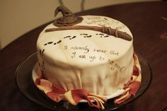 """Harry Potter cake of Marauder's Map, Sorting Hat, and wand.  Made with marbled fondant on top to replicate """"old map"""" feel, and checkerboard with Gryffindor colors on inside."""