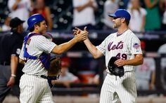 Jonathon Niese #49 of the New York Mets celebrates the final out against the Philadelphia Phillies with teammate Travis d'Arnaud #15 at Citi Field on August 27, 2013 in the Flushing neighborhood of the Queens borough of New York City.