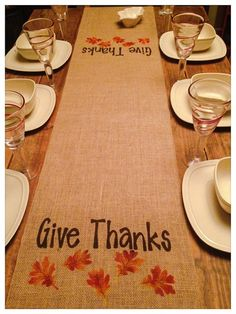 Burlap table runner with Give Thanks painted across the runner twice with a leaf pattern below each of the Give Thanks in the center of the