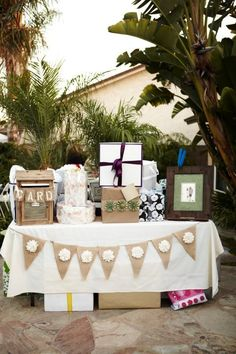 gift table with banner, pom poms hanging above and chalk board that says 'o you shouldn't have'