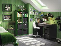 Dormitorio con un escritorio negro a juego con una cajonera con ruedas y una estantería verde con cajas negras.