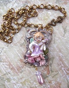 FUF 5/15 ; B'Sue chain and Victorian style frame colored with Inka Gold/Perfect Pearls/Dye oxide and Christie Friesen pearly white mica powder, ceramic roses some colored with PP to, bell caps, no hole pearls and vintage violet/mauve faux pearl drop with a Czech bell flower cap. Harry vintage broken porcelain doll, I had to fill her bottoms up with flowers!