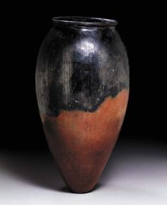 AN EGYPTIAN BLACK-TOPPED POTTERY JAR   Predynastic Period, Circa 3200 B.C.   The tall ovoid body with a flared rim and a flat base, the surface burnished  16 1/8 in. (40.9 cm) high