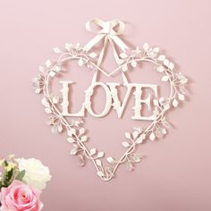 A heart shaped wall hanging made from powder coated metal featuring leaves and vines woven around it and adorned with crystal beads Complete with hanging holes to the back of the piece, this will look great in any room in the home The neutral ivory colour will complement existing interior design