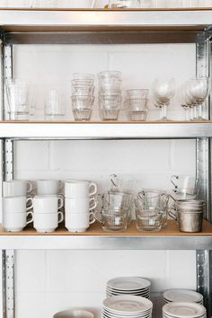 Clear glass tumblers and white ceramic teacups and saucers on stainless steel industrial shelves at the Rye London kitchen - storage ideas Glass Shelves Ikea, Glass Shelves In Bathroom, Kitchen Shelves, Kitchen Storage, Kitchen Corner, Kitchen Organization, Kitchen Cabinets, New Furniture, Kitchen Furniture