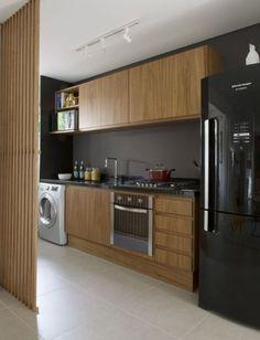 A parede preta (ou cinza)  dá destaque ao armário de madeira