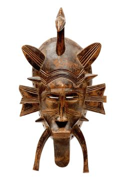 Africa | A Senufo mask. Burkina Faso | Kpelie, the face displays a prominent arch of the eyebrow, slit eyes, a stylized nose and a protruding rectangular mouth bearing the teeth. A bird's head arises from the top of the head and scarified growths emerges from the sides and chin. This senufo mask symbolizes the ordered world through its delicate shape. It is used during funeral rituals to summon the spirit of the dead to leave his home.
