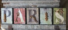Aged wooden letters spell Paris, each letter features a metal accent piece. (Please note: these letters are very chippy and distressed, for a vintage look). Each letter is 8
