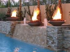 WOW - mini fire pits incorporated in the pool & water feature design. Definitely a talking point when entertaining!