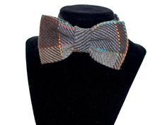 Four. Brown and multi colored plaid pre-tied bow tie with adjustable strap.