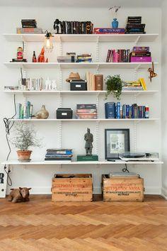 Weißes Buchregal mit Lampe, Holzkisten und anderen Accessoires