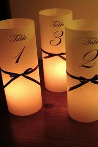 Great way to light up the tables & show table numbers. Can also have bride & grooms initials, monogram, etc instead. Scrapbook paper rolled with black ribbon & battery tea light