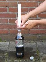 houd de rol papier boven de fles met je hand ertussen