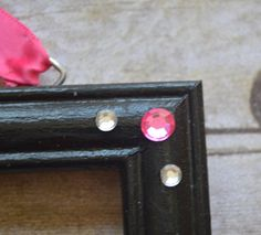 The perfect way to organize your little girls hair bows and decorate the nursery all at the same time! Measuring 9X11 this is a great place to display and organize all your little girls hair bows. There are also white hooks along the bottom to hang all of her fashionable headbands. This particular one is a black frame with pink ribbon and pink zebra print ribbon! The embellishment on the hair bow holder is a black pink and white flower with pink and white rhinestones. The hanging ribbon is…