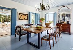 In a dining room of a Greek-island family complex, a Nikos Nikolaou painting is displayed behind a Greek bench cushioned with a lively mix of fabrics.