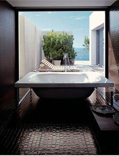 salle de bains moderne avec une baignoire îlot carrée et chaise longue en bois