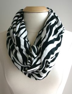 As you may have noticed, I'm addicted to scarves! In my last scarf post, I used a pretty pin to attach the ends together and instantly made an infinity scarf. With this large zebra print scarf, I decided to stitch the ends together. This scarf had fringe on the ends, and I contemplated tying the fringe together, but was determined to use my sewing machine! I tied fringe on scarf #2. Scroll all the way down to see how that one turned out! Scarf #1 Step 1. Pin the right sides together at the…