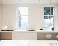 In his spare, ultracontemporary, and all-white kitchen in Piacenza, Italy, lighting designer Davide Groppi suspended his Less Is Less pendants over the dining table. Architects Simone Subitoni and Silvia Blesi pared down the room to its bare essentials, with a range, a sink, and a home office.