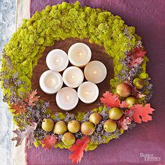 Forget evergreens! Halo a candle collection with a beautiful fall wreath made of moss and other natural elements. Use a foam wreath base and hot-glue the moss to all sides. Decorate as desired, and center it on the table around candles. Light and enjoy!/