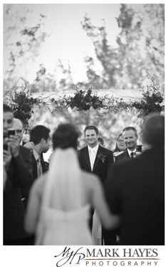 A groom watching his soon to be wife come down the isle