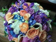 Bright and vibrant bridal bouquet of lavender and orange roses, coral ranuculas , queen annes lace, purple stock, blue hydrangea , picasso calla lily and a touch of white freesia....with Daevids of Norfolk