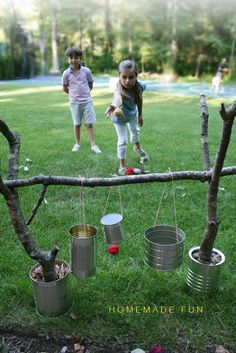 Make a homemade ball toss with cans, string, and sticks. Use any ball(s) you have lying around that you see fit.