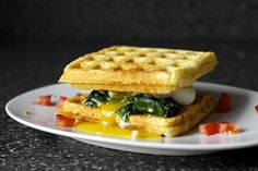 five egg sandwiches | smittenkitchen.com   [pictured here: cheddar cornbread waffle sandwich with creamed greens and a poached egg]