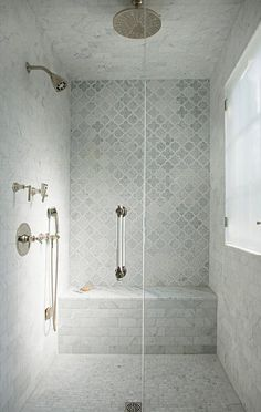 the shower wall features a center panel with accent tiles
