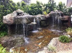 large custom artificial rock waterfall with pond