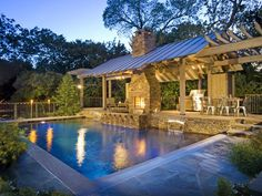 This covered outdoor patio is certainly not lacking in atmosphere. A trio of chandeliers helps create a stunning ambiance at night, especially when the light reflects off the nearby water. The patio itself houses a fully equipped kitchen and grilling area, spacious dining table, lounge and fireplace. Design by Randy Angell of Pool Environments