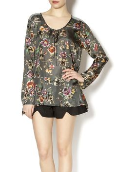 This top from Johnny Was is very beautiful, with feminine floral prints in many colors over the grey background. The lustrous silk is a nice fabric choice, and you'll love the elegant and flowing design. Long sleeves and a tie at the neck add a nice look. There are also beautiful embroidered designs on the shoulder tops. This silk tunic looks great with a nice pair of jeans or a simple skirt. Made by Johnny Was, this can be washed in the cold, gentle cycle of the washer. Made of 100% silk…