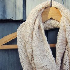 "Creamy knit yarn pairs with a sweet golden thread on this darling infinity scarf. Detailed with a tiny cable knit this scarf is perfect for chilly winter days. Perfect worn wrapped twice for the coziest fit. Width: 14"" Length: 60"""