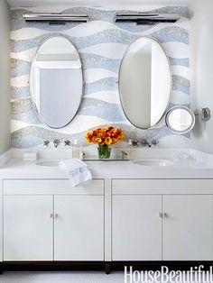 In the girls' bath, a pair of Restoration Hardware mirrors hang on top of waves of mosaic tiles, designed by James Howard.