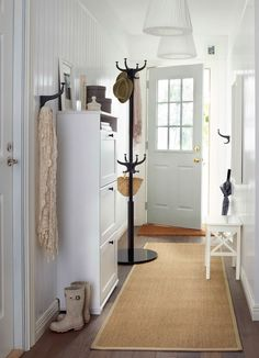 A long narrow hallway with a white shoe cabinet with space for 12 pairs of shoes, a black hat and coat stand and a white stool.
