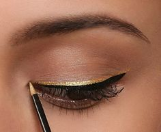 Simple yet pretty makeup look! Looks like its either skin tone eye shadow or no eye shadow at all with gold and black eye liner on the upper lash line.