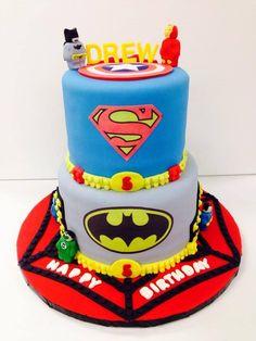Lego superhero cake featuring Lego Batman, Ironman, Green Lantern, Captain America, and Superman with Spiderman design cake board.