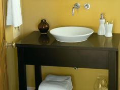 Vessel sinks are a natural choice for upcycling a piece of furniture as a bathroom vanity, because they allow you to keep more of an attractive piece's top intact. Here, a shallow porcelain sink — Kohler's Conical Bell model — atop a rustic console table is reminiscent of an old-style farmhouse washbasin.