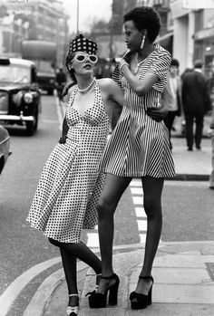 Models Endy Cartnell, in a spotted sundress and hat, and Selina, in a striped sundress and bolero with 1950's jewelry. King's Road, Chelsea, London, April 1973 | #1970s #CandySays