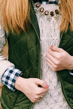 Neutral sweaters, gingham and statement necklace topped with a olive vest.